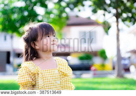 Asian Children Are Happy, Smiling Sweet And Staring At The Sky. The Background Is A Blurred House An