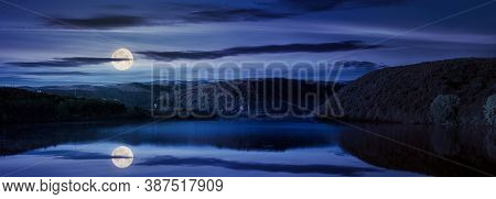 Mountain Lake Among The Forest At Night. Trees In Colorful Foliage. Beautiful Panorama In Autumn Ful