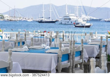 Elegant Table Setting With Fork, Knife, Wine Glass, White Plate And Blue Napkin In Restaurant . Nice