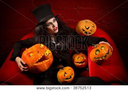 Halloween concept: sexy lady vampire with halloween pumpkins over red background