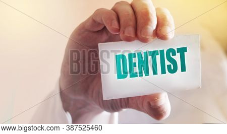 Doctor Keeps A Card With Word Dentist. Selective Focus. Medical Healthcare Concept