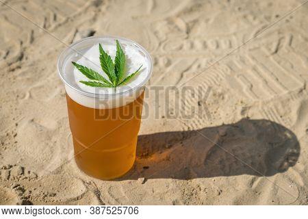 Cannabis Beer With Herbal Leaf Of Marijuana On The Foam Surface