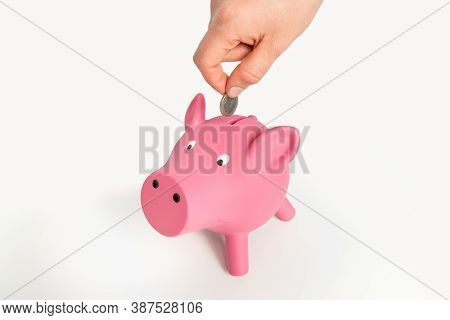 Hand Of Woman Is Putting Money In To Pink Piggy Bank - Finance Concept