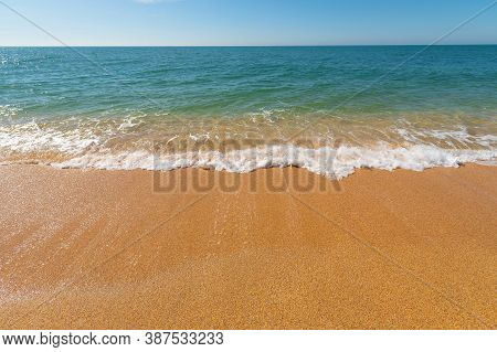 Morning Turquoise Sea And Waves With White Foam Roll Over The Yellow Golden Sand Of The Beach. Ocean