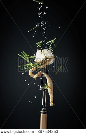 Slice Of Spicy Lard Sprinkled With Salt And Rosemary. Lard With Rosemary On A Dark Background.