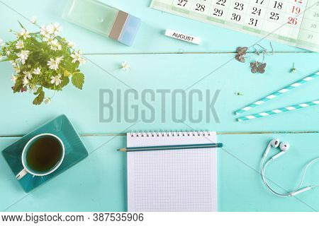 Female Flat Lay On A Blue Background, Top View Of The Desktop Of A Woman With Flowers, Pen, Notepad
