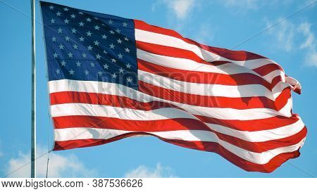 American Flag Blowing In The Wind With A Blue Sky Background. Usa American Flag. Waving United State