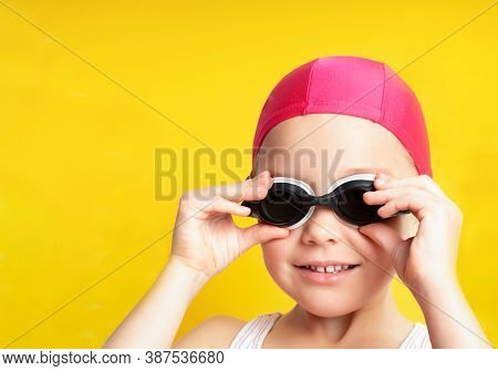 Portrait Of A Young Girl In Goggles And Swimming Cap. Isolated On Yellow Background