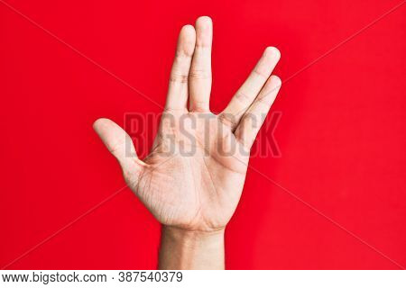 Arm of caucasian white young man over red isolated background greeting doing vulcan salute, showing hand palm and fingers, freak culture
