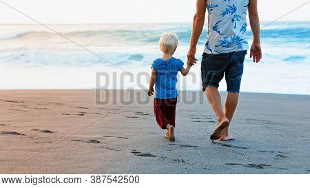 Happy Family - Barefoot Father Holds Baby Son Hand, Walk With Fun Along Sunset Sea Surf On Black San