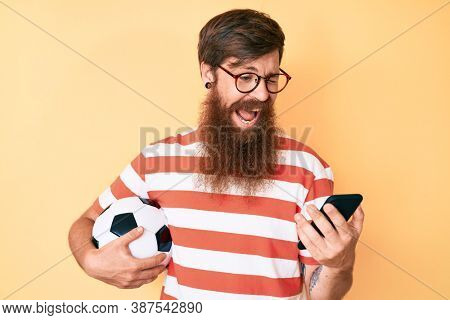 Handsome young red head man with long beard holding football ball looking at smartphone winking looking at the camera with sexy expression, cheerful and happy face.