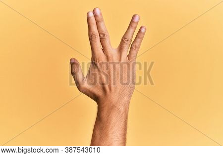 Arm and hand of caucasian man over yellow isolated background greeting doing vulcan salute, showing back of the hand and fingers, freak culture