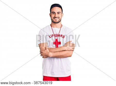 Young handsome man wearing lifeguard uniform happy face smiling with crossed arms looking at the camera. positive person.
