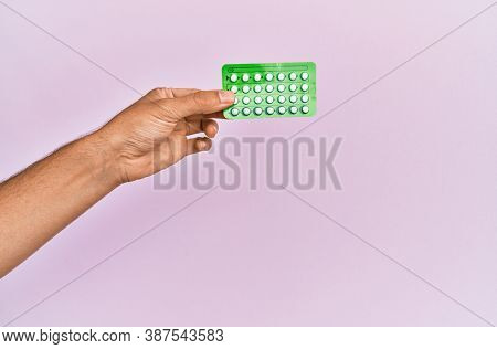 Young hispanic hand holding birth control pills over isolated pink background.