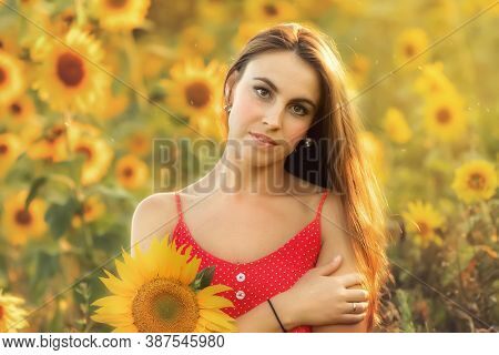 Portrait of a young woman in a field with sunflowers