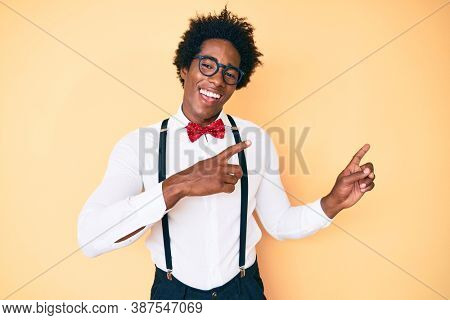 Handsome african american man with afro hair wearing hipster elegant look smiling and looking at the camera pointing with two hands and fingers to the side.