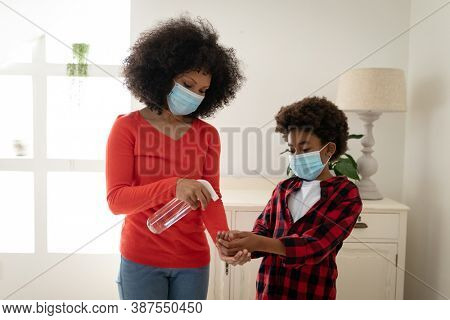 Mixed race mother with son enjoying family time together at home, social distancing and self isolation in quarantine lockdown, wearing face masks, disinfecting their hands