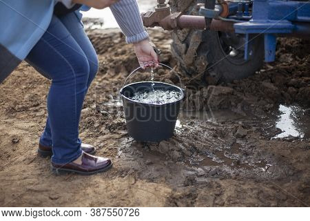 A Bucket Of Water In The Hands Of A Woman. The Girl Pours Water Into A Bucket From A Sprinkler. Disp