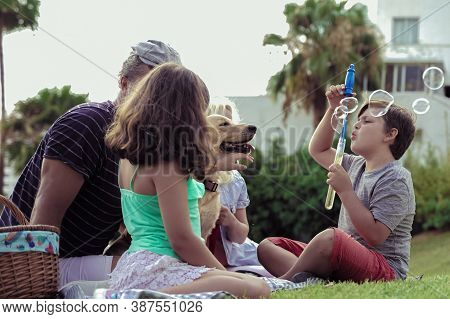 Happy Family With Their Dog In A Good Sun Day. The Boy Playing With Soap Bubbles. Happy Family Doing