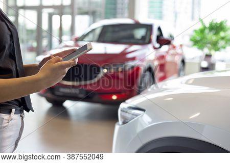 Woman Dealer Using Mobile Smart Phone At Dealer Showroom. Modern Working Process.