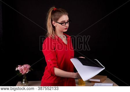 Thoughtful Female Teacher Dressed In Red Costume. European Formal-dressed Woman Is Holding A Copyboo