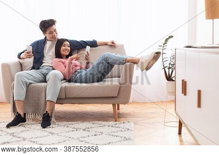 Asian Millennial Couple Using Smartphones Relaxing Sitting On Couch At Home On Weekend. Gadget Lifes