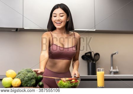 Slim Asian Woman In Fitwear Cooking Fresh Vegetable Salad For Dinner Standing In Kitchen Dieting At