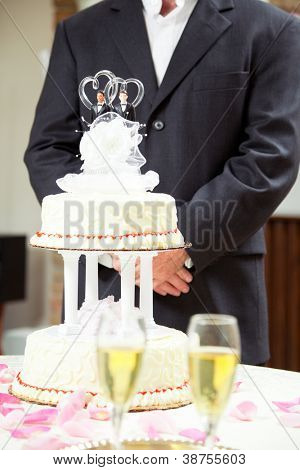 Closeup of wedding cake with champagne in the foreground and a groom in background.  Cake has two grooms - gay wedding theme.