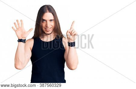 Young adult man with long hair wearing goth style with black clothes showing and pointing up with fingers number six while smiling confident and happy.