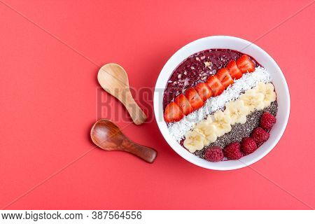 Smoothie Bowl Or Acai Berry Bowl With Chia, Strawberries, Raspberries, Banana Slices And Coconut Fla