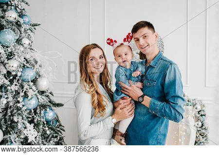 The Dad, Mom Hug Little Daughter Near Christmas Tree. Happy New Year And Merry Christmas. Christmas
