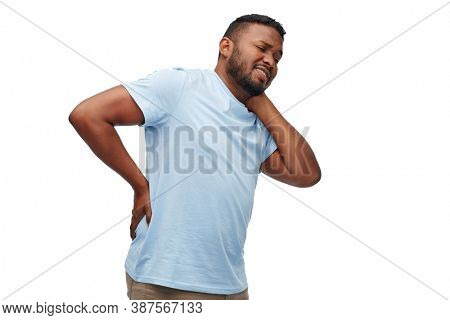 health problem and people concept - unhappy african american man suffering from pain in lower back or reins over white background
