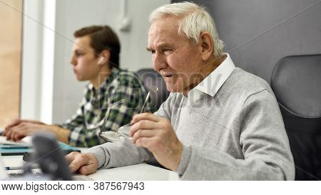 Close Up Of Aged Man, Senior Intern Looking Focused While Using Laptop, Sitting At Desk, Working In