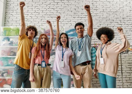 Young Diverse Volunteer Group Raised Their Arms While Posing In Front Of Boxes Full Of Clothes, Happ