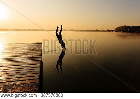 Silhouette Of Healthy Fit Man Plunge Into Water From Pier