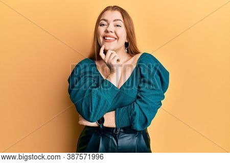 Young beautiful redhead woman wearing elegant and sexy look looking confident at the camera with smile with crossed arms and hand raised on chin. thinking positive.