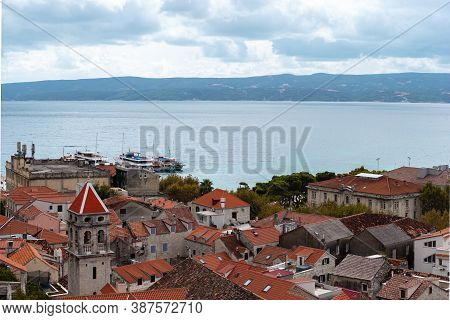 View Of The Omis City In Croatia. Small Old Stone Houses With Red Roofs, Church Belltower Peeking Ab
