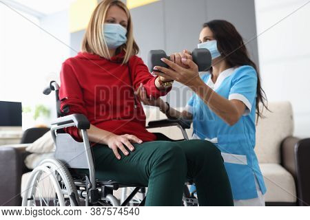 Physiotherapist Doctor In Medical Mask Helps To Raise Dumbbell To Disabled Woman In Wheelchair At Ho