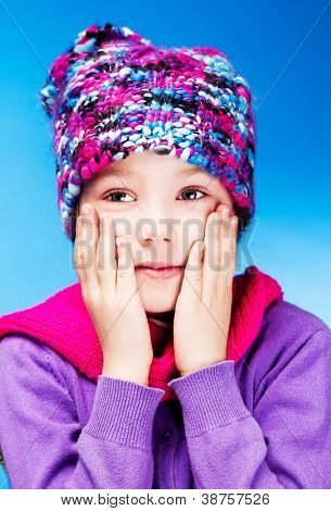 seven year old girl wearing a warm winter hat, against blue studio background