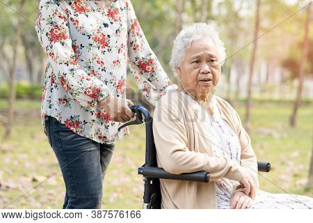 Asian Senior Or Elderly Old Lady Woman Smile Bright Face Patient On Wheelchair In Park.