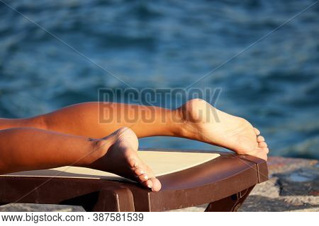 Tanning, Beach Relax And Vacation. Close Up Of Tanned Female Feet On Deck Chair On Blue Sea Backgrou
