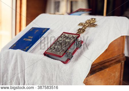 The Sacrament Of Baptism In The Orthodox Church. Prayer Books And A Crucifix On The Table.