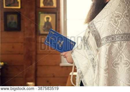 A Priest Holds A Book For Reading Prayers During The Rite Of Baptism In The Orthodox Church. Inscrip