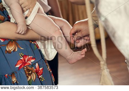 The Sacrament Of Baptism In The Orthodox Church. The Priest Anoints The Childs Feet With Oil.