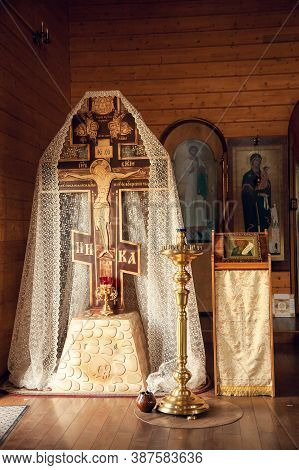 Large Cross With The Crucifixion Of Jesus Christ, Candle Stand And Icons In The Orthodox Church.