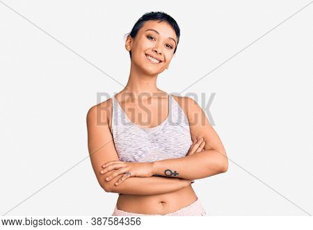 Young woman wearing sportswear happy face smiling with crossed arms looking at the camera. positive person.