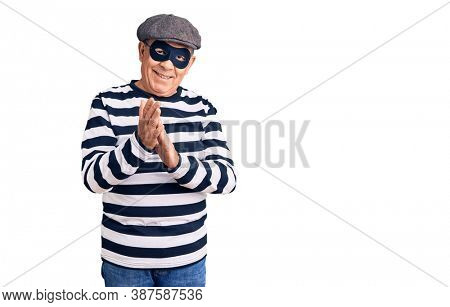 Senior handsome man wearing burglar mask and t-shirt clapping and applauding happy and joyful, smiling proud hands together