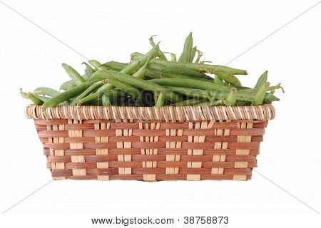 green beans in a straw basket isolated on white