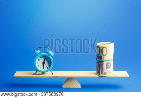 Blue Alarm Clock And A Bundle Of Euro On Scales. Fair Hourly Wages. Profitability And Return On Inve