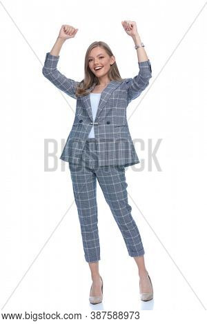 enthusiastic girl in blue checkered suit holding arms above head and cheering, laughing and standing isolated on white background, full body